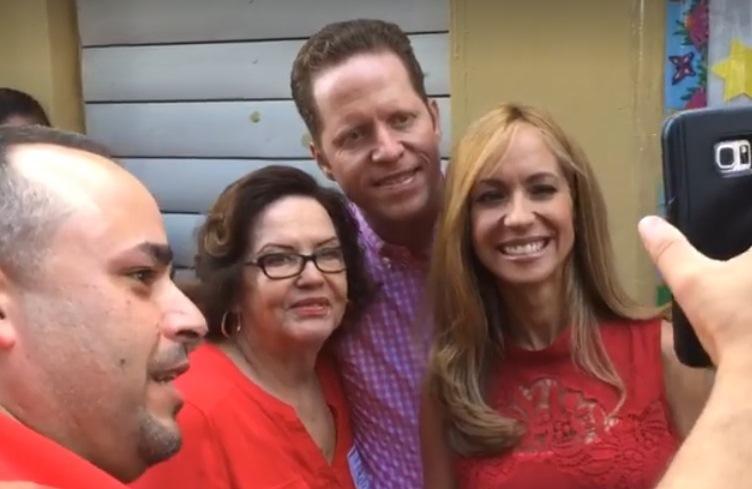 El doctor David Bernier y su esposa Alexandra Fuentes, posan junto a electores mientras esperaban para votar (Captura de pantalla/Radio Isla).
