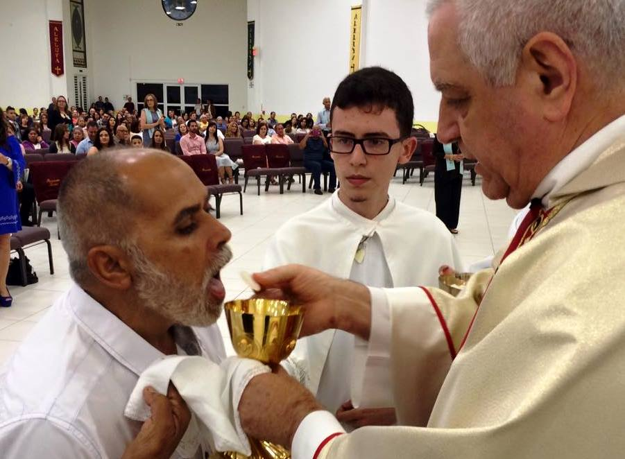 El Padre Gabela dándole la comunión a un feligrés (Foto Parroquia San Francisco de Asís de Aguada).